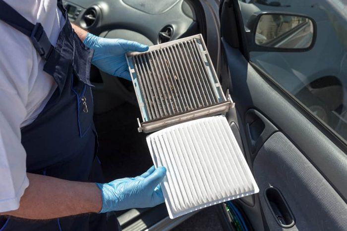 a man holding car filters with both of his hands