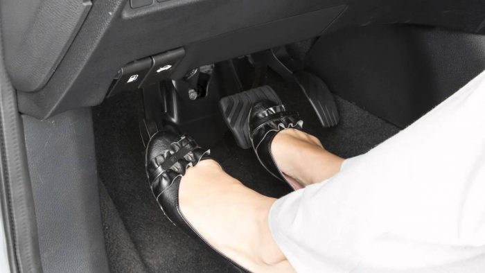 A woman placing her feet on car pedals