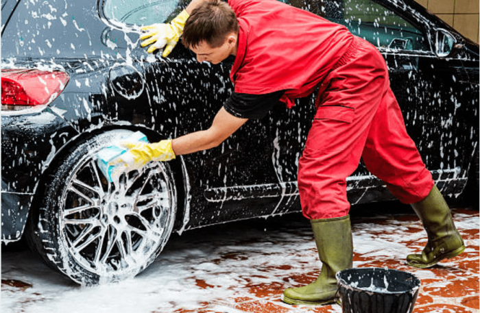 a white male washing a black car with soap