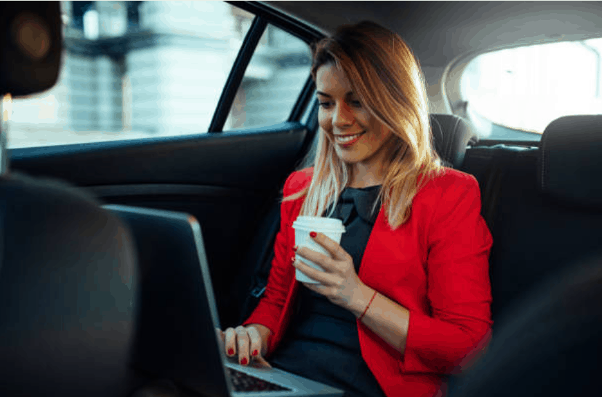 White female woman with a cup of coffee in her left hand. She is seated in the back of a vehicle with a laptop on her lap. Her right hand is on the touch pad of the laptop.