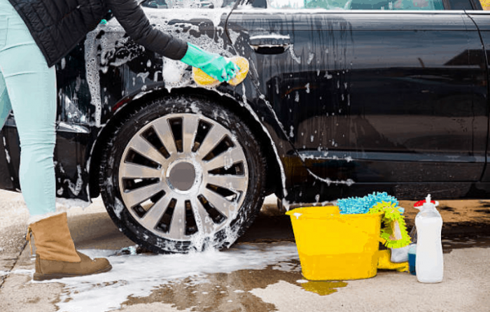someone washing a black car with a sponge and soap with a yellow bucket on the ground with other car washing items close to the bucket.