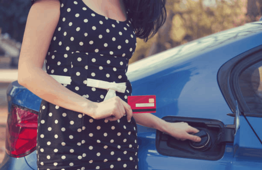 Woman wearing a polka dot blue dress closing the gas tank of a blue car holding a credit card in her right hand.