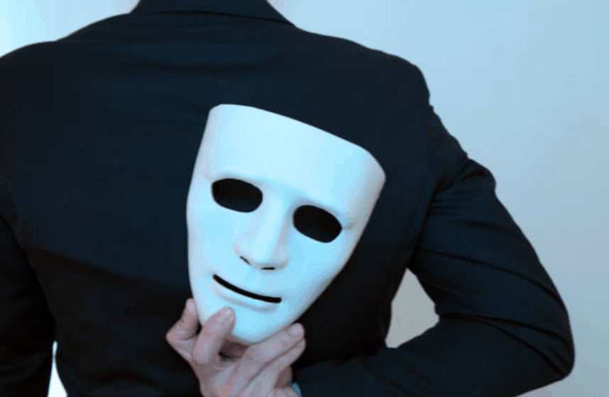 woman wearing a black jacket with her back turned and a white face mask is held with her right hand on her back