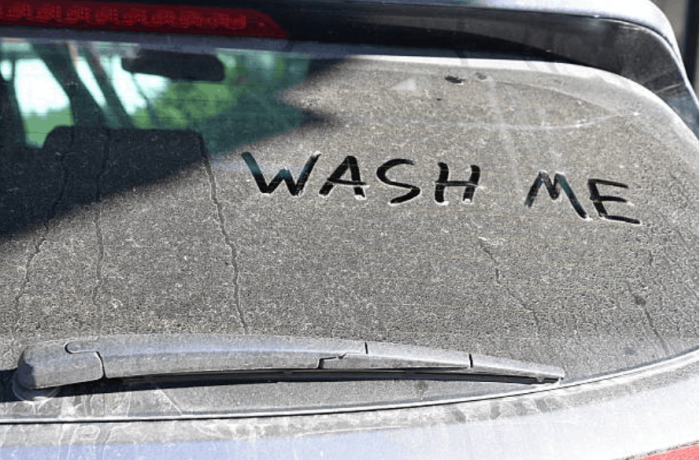 the rear glass of a car with the words wash me written on it.