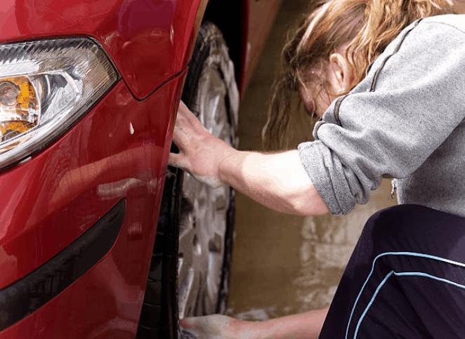 white female woman with blonde hair stooping down, washing the wheel of a red vehicle.
