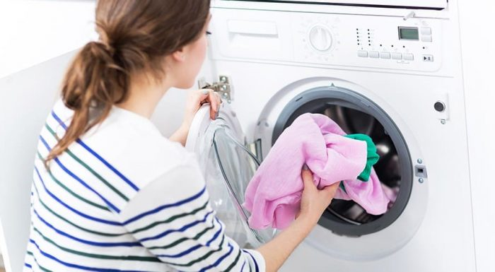 white female placing laundry in a washing machine.