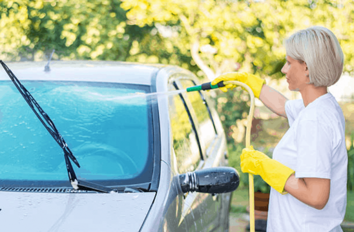 white female washing the front glass of a car with a water hose.