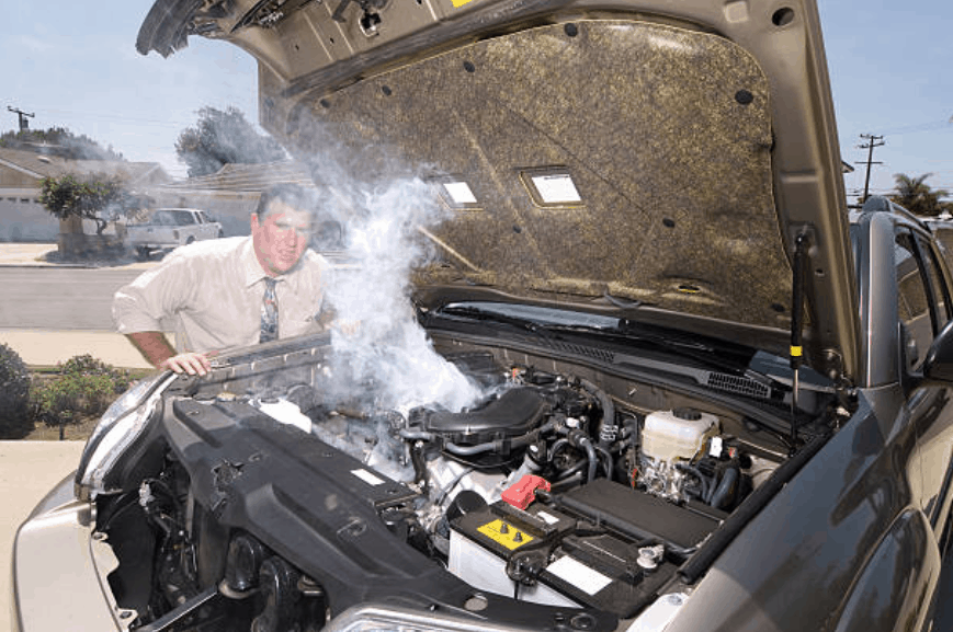 White male standing over open vehicle hood. The engine of the vehicle is smoking.